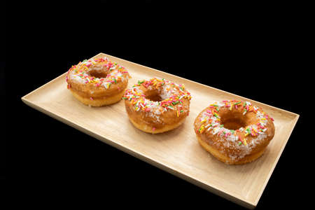 Traditional sugar donuts with multi color sprinkles on a wooden plate.
