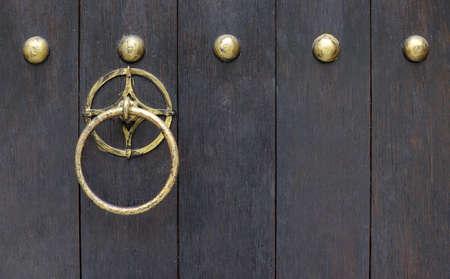 Shining solid brass metal round door knocker on old dark wooden door.