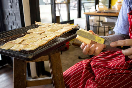 A baker preparing pieces of butter sugar coated bread for baking.