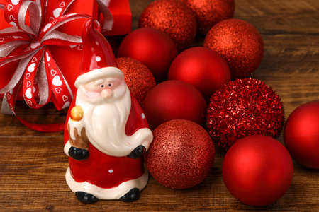 A ceramic Santa with red Christmas baubles and present boxes on wooden background. Фото со стока