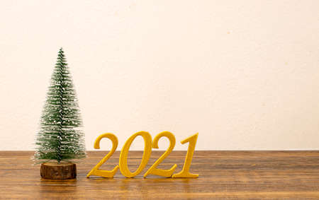 Close-up of wooden numbers 2021 painted in gold with a small handmade Christmas tree.