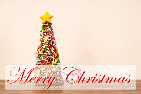 A chocolate cone in a shape of a Christmas tree coated wth multi colors sugar sprinkles with a Merry Christmas banner.