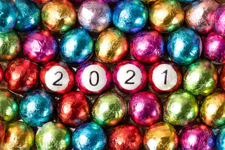 Closeup of multicolored chocolate candy balls with 2021 numbers. Фото со стока