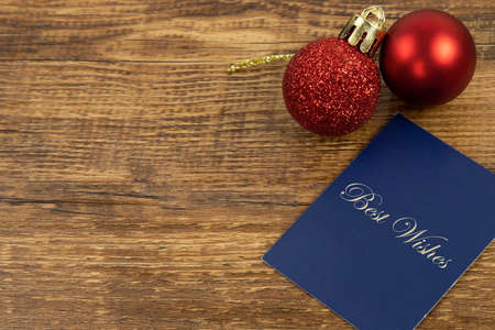 Two red Christmas baubles and a blue car with gold Best Wishes letters. Фото со стока