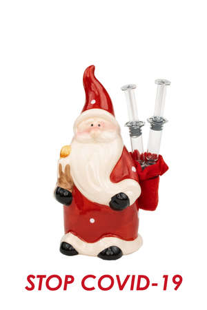 A ceramic Santa with two glass syringes in a red bag with STOP COVID-19 text message on white background.
