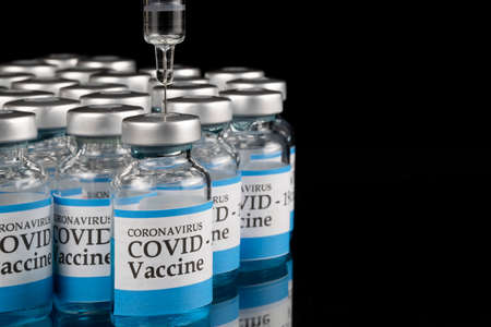 Glass vials labelled with COVID-19 text and a glass syringe on black background. Covid-19 vaccination concept. Фото со стока