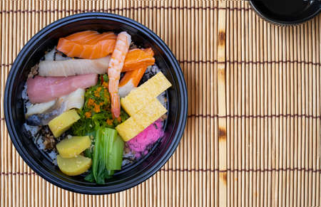 Closeup of Japanese donburi dish with fresh salmon, tuna, pacific yellowtail, pickled mackerel, grilled eel, sweet egg, and seaweeds decorated with pickled vegetables on a traditional bamboo mat. Фото со стока