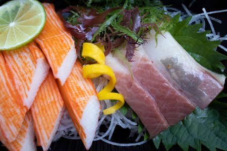 Closeup of Japanese sushi dish with fresh salmon, tuna, octopus and seaweeds decorated with spiral orange peel and a slice of lime