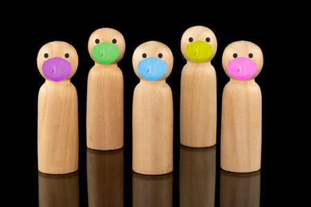 Wooden models standing apart and wearing colorful face masks  Social distancing and mask wearing concepts.