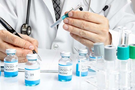A doctor holding a glass syringe writing the test result on a notebook with more vials labelled covid-19 vaccine and some test tubes in a rack on a white table. Covid-19 vaccine testing concept.