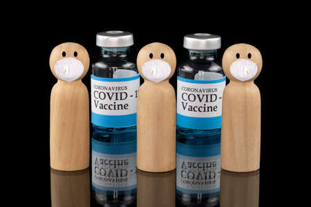 Wooden models wearing white face masks with glass vials labelling Covid-19 vaccine.