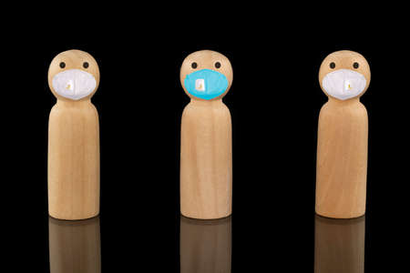 Wooden models wearing blue and white face masks. Social distancing concepts.