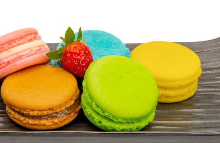 Colorful macaroon french dessert with fresh strawberry on a brow ceramic plate.