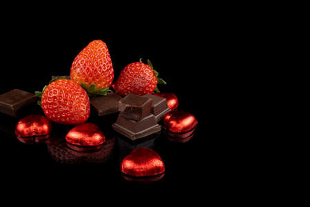 Chocolate nuggets, fresh strawberries and heart shaped chocolate candies. Love and Valentine's Day concept.