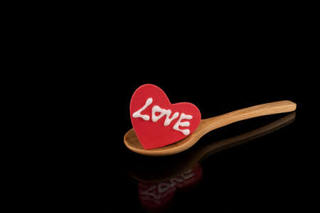 A piece of sugar icing heart with a word spelling love on a natural wooden spoon. Valentine's Day concept.