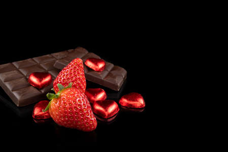 Chocolate bar, fresh strawberries and heart shaped chocolate candies. Love and Valentine's Day concept.