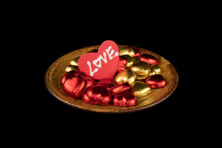 Red and gold heart shaped candies on an orange ceramic plate with a piece of sugar icing heart with white letters spelling love. Valentine's Day concept.