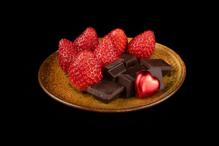 Chocolate nuggets, fresh strawberries and a heart shaped chocolate candy. Love and Valentine's Day concept. Фото со стока