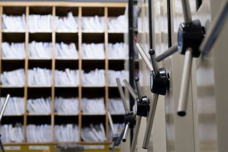 Close up on rotary handle of movable high capacity medical records storage shelves.