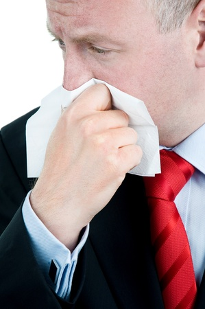Businessman with tissue suffering from cold and flu or allergy Stock Photo
