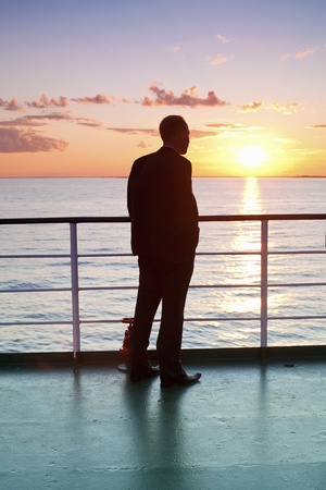 far away look: Thinking man silhouette and red sunset on a ferry