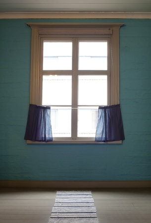 Old window with blue curtains in empty room