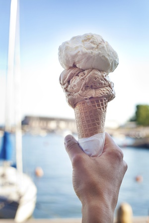 Hand holding an ice-cream cone in front of the harbour on a sunny day Stock Photo - 10797408