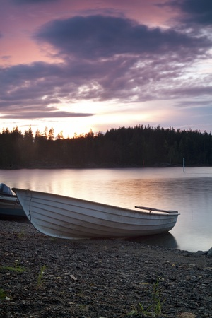 Fishing boat on the shore at evening Stock Photo