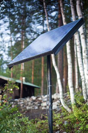 solarpanel: Close up of solar panel with small house behind