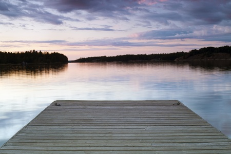 Wooden jetty over calm lake just after sunset