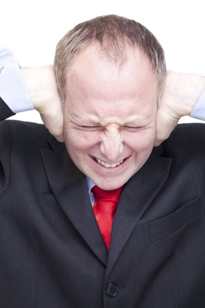 Businessman strictly covering his ears