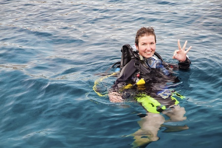 wetsuit: Portrait of a female scuba diver on the surface of the sea with diving equipment