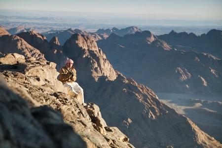 bible ten commandments: Man sitting at the edge of the mountains Sinai