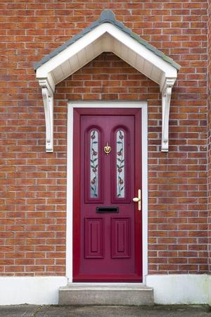 イギリスかアイルランドの家のレンガに赤いドア