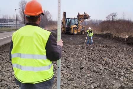 Surveyors at work with digger as background  Stock Photo - 13141729
