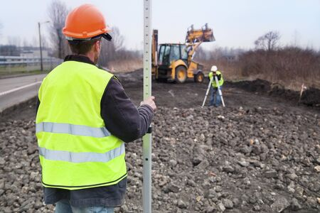 surveyors: Surveyors at work with digger as background
