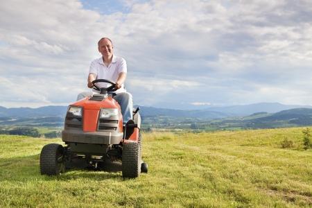 gras maaien: Man maaien zijn gazon op een rijdende grasmaaier Stockfoto