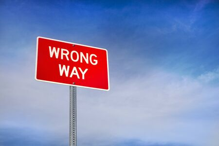 Wrong Way Road Sign and Blue Sky Behind Stock Photo