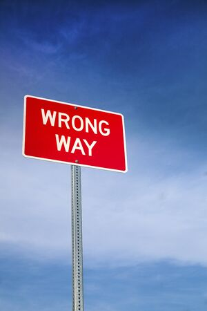 misconception: Wrong Way Road Sign and Blue Sky Behind Stock Photo