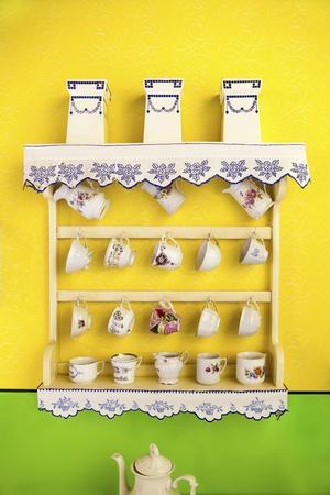 Vintage set of teacups on wooden shelf photo