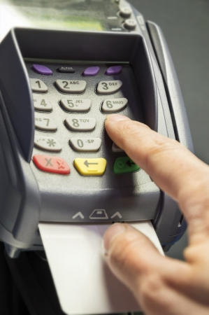 Person entering pin code at credit card reader and white, empty credit card photo