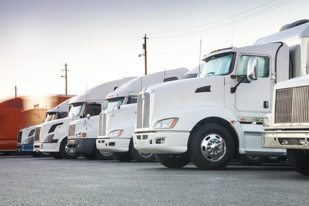 Different american trucks in a row with one which has just started its trip  Stock Photo