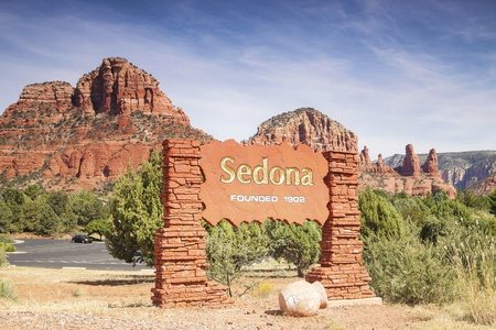 A public sign welcoming visitors to Sedona with the famous red rocks in the background