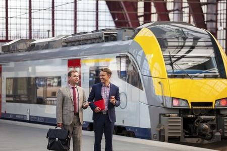 estacion tren: Dos generaciones de hombres de negocios hablando