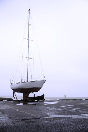 Sailboat in a harbor during autumn and winter photo