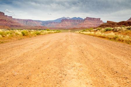 Dirt road through beautiful barren land, Utah, USA photo
