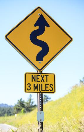 Winding road next 3 miles, warning road sign photo