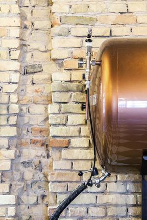 Small tank of beer nexy to brick wall photo