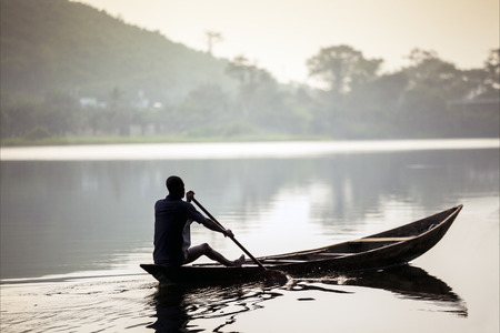 African man riding a traditional, wooden canoe in Ghana, Africa