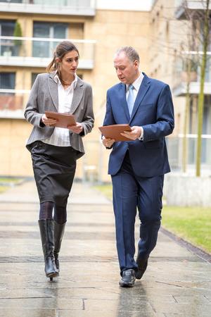 personas caminando: Dos hombres de negocios a pie y en discusiones fuera de la oficina